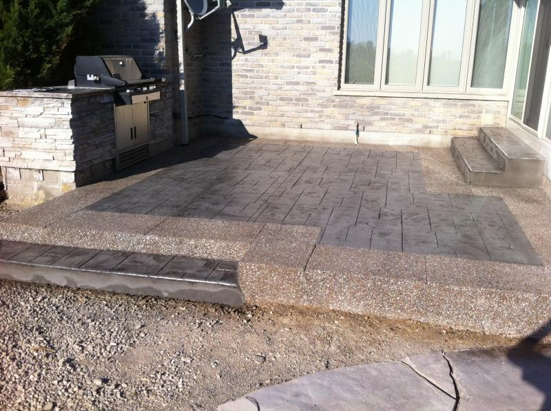 Small Ashlar Slate Stamped Concrete Patio with Exposed Aggregate Border and Step